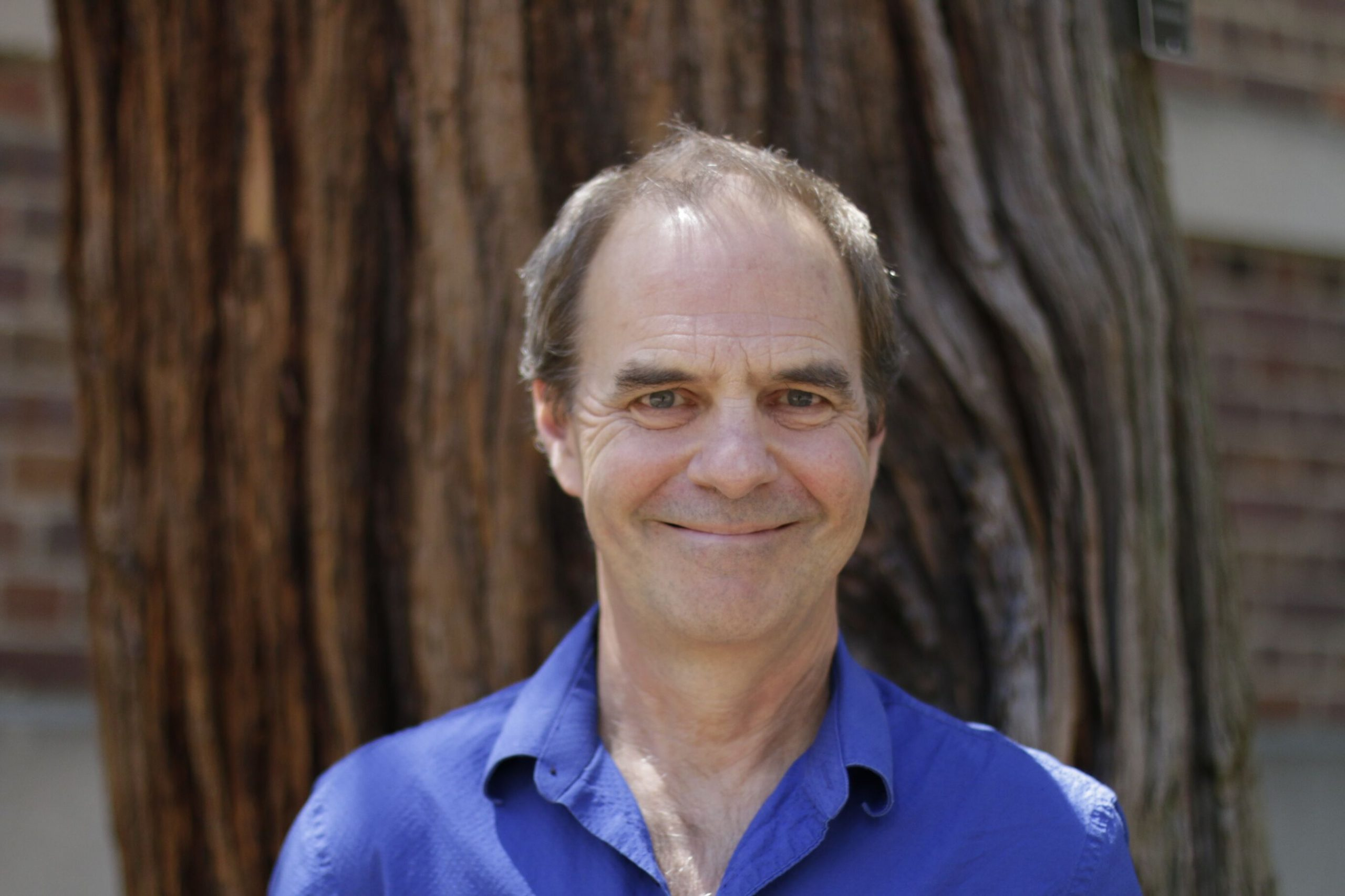Headshot of Dan Anderson, man in a blue shirt in from of a tree